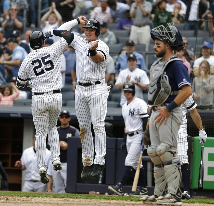 New York Yankees' Gleyber Torres (25) celebrates his two-run homer with Luke Voit, second from right, during the seventh inning of a baseball game against the San Diego Padres at Yankee Stadium, Wednesday, May 29, 2019, in New York. (AP Photo/Seth Wenig)