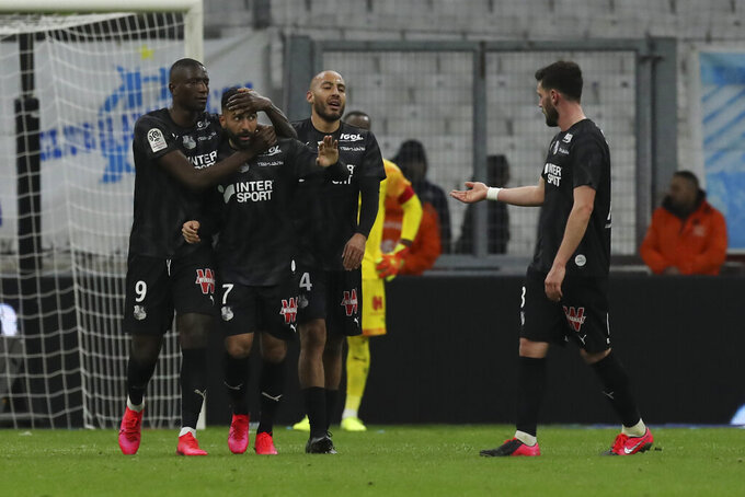 Amiens' Saman Ghoddos, second left, celebrates with teammates Serhou Guirassy, left, and Haitam Aleesami, second right, after scoring his side's second goal during the French League One soccer match between Marseille and Amiens at the Velodrome stadium in Marseille, southern France, Friday, March 6, 2020. Ghoddos and Guirassy scored once each and the match ended in a 2-2 draw. (AP Photo/Daniel Cole)