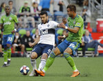 Vancouver Whitecaps' Felipe Martins (8) tries to control the ball in front of Seattle Sounders' Justin Dhillon in the first half of an MLS soccer match Saturday, June 29, 2019, in Seattle. (AP Photo/Elaine Thompson)