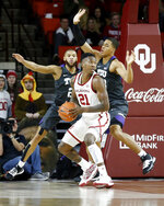 Oklahoma's Kristian Doolittle (21) is defended by TCU's Edric Dennis Jr. (2) and Jaedon Ledee (23) during the first half of an NCAA college basketball game in Norman, Okla., Saturday, Jan. 18, 2020. (AP Photo/Garett Fisbeck)