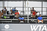 Coaches and tournament personnel practice social distancing during the WTA tennis tournament in Nicholasville, Ky., Thursday, Aug. 13, 2020. Fans were not allowed in to watch the action. (AP Photo/Timothy D. Easley)