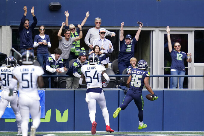 Fans cheer as Seattle Seahawks wide receiver Tyler Lockett (16) scores a touchdown in front of Tennessee Titans inside linebacker Rashaan Evans (54) during the first half of an NFL football game, Sunday, Sept. 19, 2021, in Seattle. (AP Photo/Elaine Thompson)
