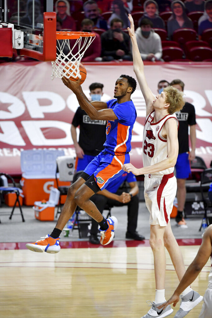 Florida guard Scottie Lewis (23) drives past Arkansas defender Connor Vanover (23) during the second half of an NCAA college basketball game in Fayetteville, Ark. Tuesday, Feb. 16, 2021. (AP Photo/Michael Woods)