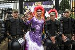 A gay and lesbian rights activist stands between Ukrainian police guards during the annual Gay Pride parade, protected by riot police in Kiev, Ukraine, Sunday, June 17, 2018. Several thousand supporters of gay pride have held a march in Ukraine's capital that lasted about 20 minutes despite opponents attempts to block them. (AP Photo/Evgeniy Maloletka)