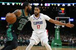 Boston Celtics' Kyrie Irving (11) drives past Los Angeles Clippers' Garrett Temple (17) during the first half of an NBA basketball game in Boston, Saturday, Feb. 9, 2019. (AP Photo/Michael Dwyer)