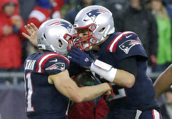New England Patriots quarterback Tom Brady, right, celebrates his touchdown pass to Julian Edelman, left, in the first half of an NFL football game against the Cleveland Browns, Sunday, Oct. 27, 2019, in Foxborough, Mass. (AP Photo/Elise Amendola)