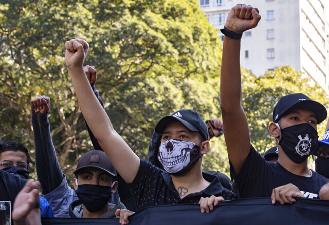 Fans of two distinct soccer clubs join forces for an anti-government protest in Sao Paulo, Brazil, Sunday, May 31, 2020. Police used tear gas to disperse anti-government protesters in Brazil's largest city as they began to clash with small groups loyal to President Jair Bolsonaro. (AP Photo/Andre Penner)