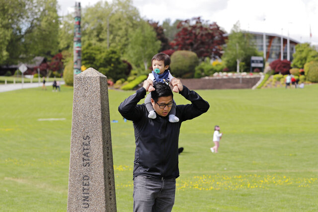 In this photo taken Sunday, May 17, 2020, Bryan Albano, walks with his son Zachary atop his shoulders in Canada at Peace Arch Provincial Park, adjacent to Peace Arch Historical State Park on the U.S. side, where people can walk freely between the two countries at an otherwise closed border, in Blaine, Wash. Canada and the U.S. have agreed to extend their agreement to keep the border closed to non-essential travel to June 21 during the coronavirus pandemic. The restrictions were announced on March 18, were extended in April and now extended by another 30 days. (AP Photo/Elaine Thompson)