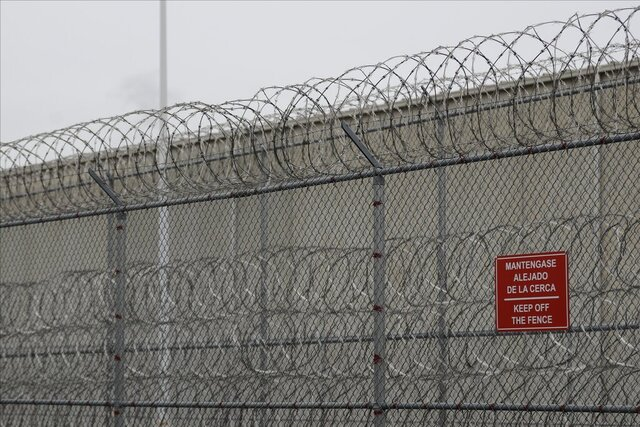 FILE - In this Dec. 16, 2019, file photo, barbed wire fencing is shown behind a sign in English and Spanish in a recreation yard used by detainees during a media tour of the U.S. Immigration and Customs Enforcement detention center, in Tacoma, Wash. A federal judge has declined on Friday, Dec. 18, 2020, to order speedier bail hearings for detainees at the U.S. Immigration and Customs Enforcement lockup in Tacoma, who are especially at risk from COVID-19, despite a few recent cases there. (AP Photo/Ted S. Warren, File)