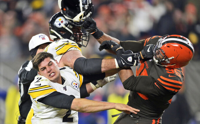Cleveland Browns defensive end Myles Garrett hits Pittsburgh Steelers quarterback Mason Rudolph (2) with a helmet during the second half of an NFL football game, Nov. 14, 2019, in Cleveland. (AP Photo/David Richard)