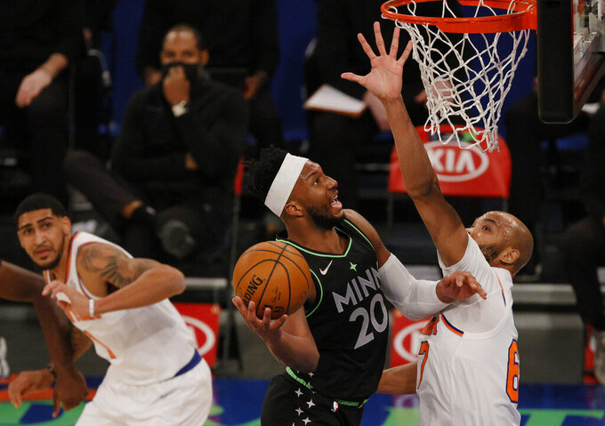Josh Okogie, center, of the Minnesota Timberwolves shoots as Taj Gibson, right, and Obi Toppin, left, of the New York Knicks defend during the first half of an NBA basketball game Sunday, Feb. 21, 2021, in New York. (Sarah Stier/Pool Photo via AP)