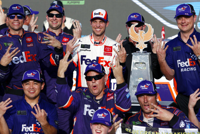 Denny Hamlin, center, and his race team in victory lane after winning the NASCAR Cup Series auto race at ISM Raceway, Sunday, Nov. 10, 2019, in Avondale, Ariz. (AP Photo/Ralph Freso)