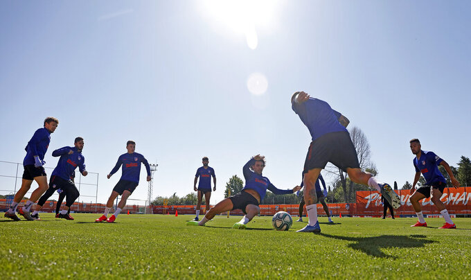 In this photo provided by Atletico Madrid, team players take part in the first group training session in Madrid, Spain, on Monday May 18, 2020. All Spanish league clubs can begin group training sessions this week despite stricter lockdown restrictions remaining in place in parts of Spain because of the coronavirus pandemic. (Atletico de Madrid via AP)