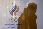 FILE - In this Nov. 18, 2015 file photo a man walking past the Russian Olympic Committee building, casts a shadow on a window in Moscow, Russia. The World Anti-Doping Agency banned Russia on Monday Dec. 9, 2019 from the Olympics and other major sporting events for four years, though many athletes will likely be allowed to compete as neutral athletes. (AP Photo/Pavel Golovkin, file)
