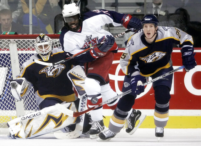 "FILE - In this Jan. 12, 2007, file photo, Nashville Predators center Jerred Smithson (25) clears the puck away from Columbus Blue Jackets right wing Anson Carter, center, in the first period of an NHL hockey game in Nashville, Tenn. Carter played a decade in the NHL and has since become an analyst for NBC Sports, which will launch ""Hockey Culture"" with him at the center of the show. (AP Photo/Mark Humphrey, File)"