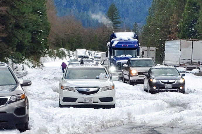 In this photo provided by Caltrans, are cars and trucks in stopped traffic on Interstate 5 near Dunsmuir, Calif., Wednesday, Nov. 27, 2019. Thanksgiving travel has been snarled in some places by two powerful storms. A winter storm blamed for one death and hundreds of canceled flights in the West moved into the Midwest on Wednesday and dropped close to a foot of snow in parts of Minnesota and Wisconsin. (Caltrans via AP)