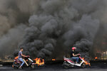 Men on scooters pass tires that were set on fire to block a road during a protest against government's plans to impose new taxes in Beirut, Lebanon, Friday, Oct. 18, 2019. The protests erupted over the government's plan to impose new taxes during a severe economic crisis, with people taking their anger out on politicians they accuse of corruption and decades of mismanagement. (AP Photo/Hassan Ammar)