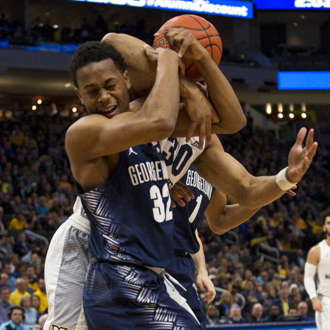 Georgetown guard Kaleb Johnson, left, battles for the rebound with Marquette forward Ed Morrow, right, during the first half of an NCAA college basketball game Saturday, March 9, 2019, in Milwaukee. (AP Photo/Darren Hauck)
