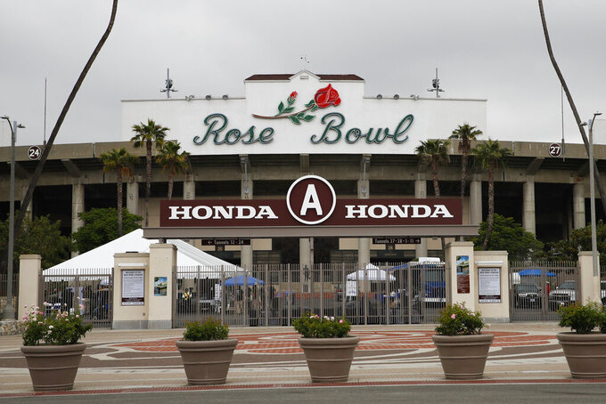 FILE - In this May 10, 2017, file photo, members of the media gather outside the Rose Bowl Stadium in Pasadena, Calif. No spectators will be allowed at the Rose Bowl for the College Football Playoff semifinal on Jan. 1 because of COVID-19 restrictions imposed by the state, county and city of Pasadena, The Tournament of Roses said Thursday, Dec. 3, 2020. (AP Photo/Jae C. Hong, File)