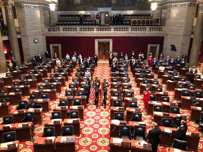 A Color Guard enters the Missouri House chamber to open the 2021 legislative session on Wednesday, Jan. 6, 2021, in Jefferson City, Missouri. Only the more senior incumbent lawmakers were present in order to try to reduce the number of guests in the galleries as a COVID-19 precaution. Newer lawmakers were later added to the floor, filling up the chamber. (AP Photo/David A. Lieb)
