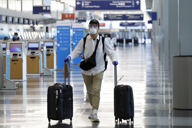 FILE - In this June 16, 2020 file photo, a traveler wears a mask and protective goggles as he walks through Terminal 3 at O'Hare International Airport in Chicago. United Airlines says its face mask requirement now extends to ticket counters and airport lounges. United said Wednesday, July 22 that it might ban violators from flying on its planes. United and all other major U.S. airlines already require passengers to wear masks during flights. (AP Photo/Nam Y. Huh, File)