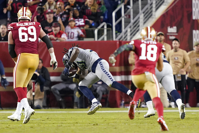 Seattle Seahawks defensive end Jadeveon Clowney, center, returns a fumble for a touchdown against the San Francisco 49ers during the first half of an NFL football game in Santa Clara, Calif., Monday, Nov. 11, 2019. (AP Photo/Tony Avelar)