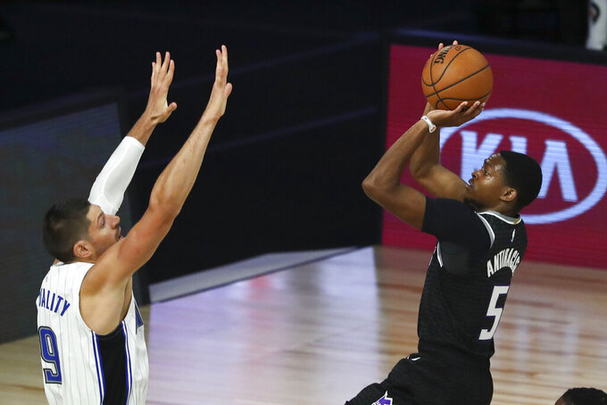 Sacramento Kings guard De'Aaron Fox (5) shoots as Orlando Magic center Nikola Vucevic (9) defends during the first half of an NBA basketball game Sunday, Aug. 2, 2020, in Lake Buena Vista, Fla. (Kim Klement/Pool Photo via AP)