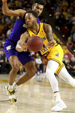 Arizona State's Kimani Lawrence (4) dishes the ball off while being covered by Washington's Jamal Bey during the second half of an NCAA college basketball game Thursday, March 5, 2020, in Tempe, Ariz. (AP Photo/Darryl Webb)