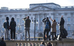 Tourists take photos outside the gates of Buckingham Palace, following a statement by Britain's Queen Elizabeth II and Buckingham Palace, in London, Sunday, Jan, 19, 2020. Buckingham Palace says Prince Harry and his wife, Meghan, will no longer use the titles
