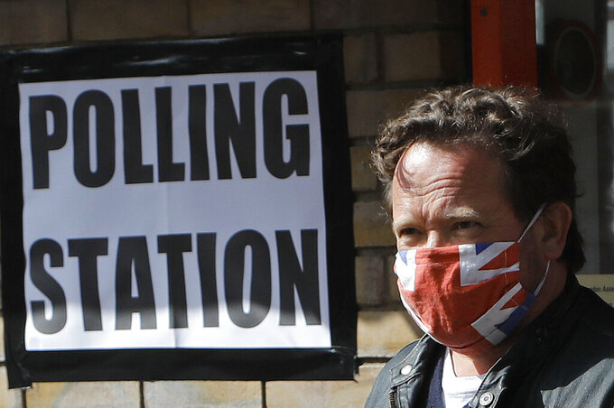 A man wearing a face covering leaves the polling station at St Albans Church after he voted, in London, Thursday, May 6, 2021. Millions of people across Britain will cast a ballot on Thursday, in local elections, the biggest set of votes since the 2019 general election. A Westminster special-election is also taking place in Hartlepool, England. (AP Photo/Frank Augstein)