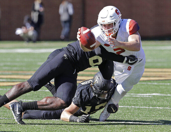 Syracuse's Eric Dungey (2) reaches for a first down as Wake Forest's Luke Masterson (12) and Chris Calhoun (6) defend in the first half of an NCAA college football game in Charlotte, N.C., Saturday, Nov. 3, 2018. (AP Photo/Chuck Burton)