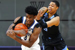 Villanova's Brandon Slater, left, tries to hang onto the ball against Marquette's Greg Elliott during the second half of an NCAA college basketball game, Wednesday, Feb. 10, 2021, in Villanova, Pa. (AP Photo/Matt Slocum)