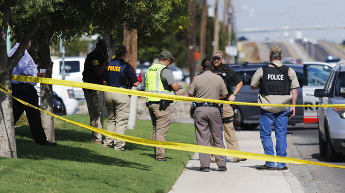 Authorities cordon off a part of the sidewalk in the 5100 block of E. 42nd Street in Odessa, Texas, Saturday, Aug. 31, 2019. Several people were dead after a gunman who hijacked a postal service vehicle in West Texas shot more than 20 people, authorities said Saturday. The gunman was killed and a few law enforcement officers were among the injured. (Mark Rogers/Odessa American via AP)
