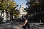 A woman wearing a face mask walks past the Sorbonne university in Paris, France, Thursday, Sept. 17, 2020. In France, overcrowded universities have seen the emergence of at least a dozen of virus hotspots, raising concerns in a country where the number of infections has steadily increased in recent weeks. (AP Photo/Francois Mori)
