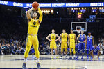 Marquette's Markus Howard (0) takes a free-throw on a technical foul on Xavier head coach Travis Steele in the second half of an NCAA college basketball game, Saturday, Jan. 26, 2019, in Cincinnati. (AP Photo/John Minchillo)