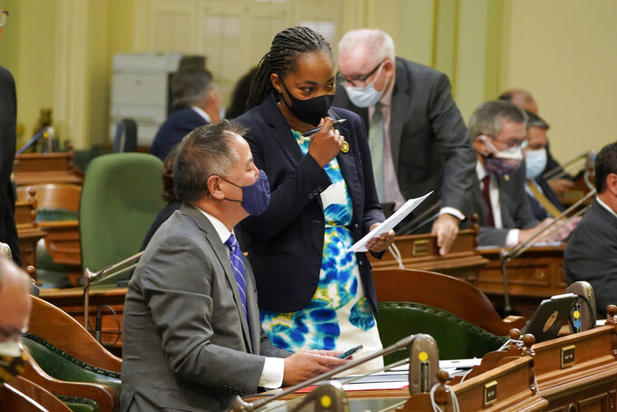 Assemblywoman Akilah Weber, D-San Diego, talks with Assemblyman Phil Ting, D-San Francisco, as the Assembly meets in Sacramento, Calif., Thursday, Sept. 2, 2021. On Friday, Sept. 3, 2021, the Assembly approved a bill, carried by Weber, that would create a mandatory new state license, or certification, that could be revoked so bad law enforcement officers cannot simply move to another department. The bill, SB2 by Democratic state Sen. Steven Bradford, now goes to the Senate. (AP Photo/Rich Pedroncelli)