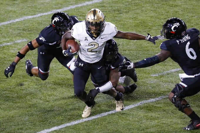 UCF running back Otis Anderson (2) carries the ball against Cincinnati linebacker Perry Young (6) during the first half of an NCAA college football game Friday, Oct. 4, 2019, in Cincinnati. (AP Photo/John Minchillo)
