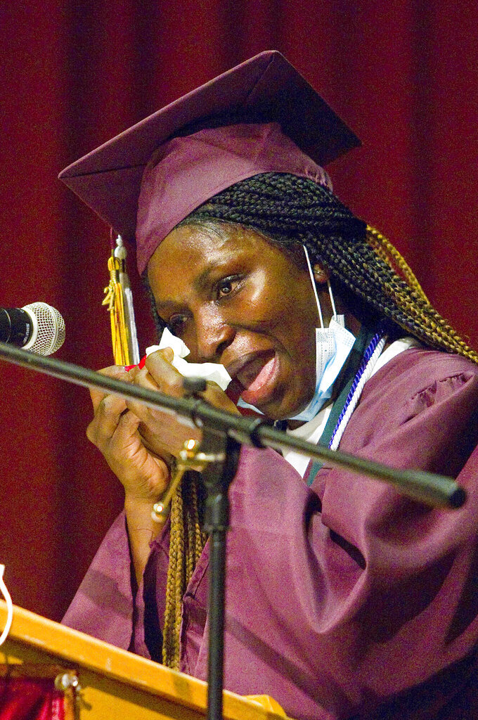 Blessing Ovie wipes tears while giving her speech during Traverse City High School's commencement on Friday evening, June 4, 2021, at Lars Hockstad Auditorium in Traverse City, Mich. Ovie, who was born in Nigeria, came to Traverse City from Morocco through a United Nations refugee minor program, and will attend Western Michigan University in the fall. (Jan-Michael Stump/Traverse City Record-Eagle via AP)