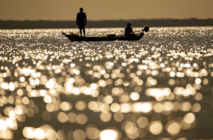 Fishermen ply their trade in the Tapajos river in Alter do Chao, district of Santarem, Para state, Brazil, Thursday, Aug. 27, 2020. The riverside region dubbed