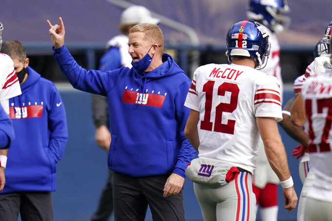 New York Giants offensive coordinator Jason Garrett gestures as he stands next to quarterback Colt McCoy (12) before an NFL football game against the Seattle Seahawks, Sunday, Dec. 6, 2020, in Seattle. Garrett's gesture is the hand sign for the University of Texas, where McCoy was the starting quarterback from 2006 to 2009. (AP Photo/Elaine Thompson)