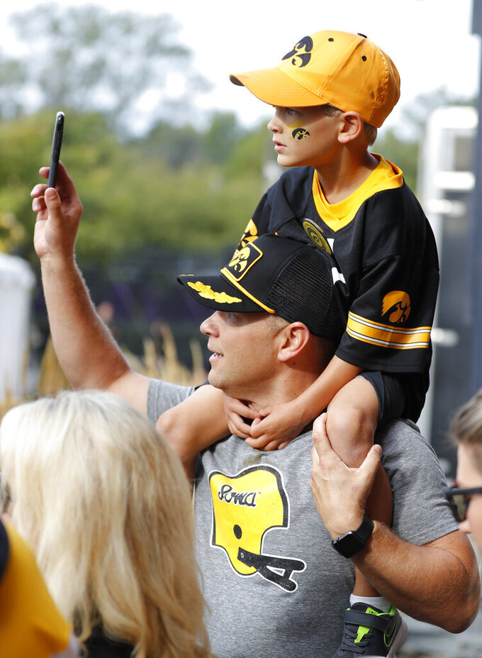 Iowa fans watche as the Hawkeyes arrive at Kinnick Stadium before the team's NCAA college football game against Rutgers, Saturday, Sept. 7, 2019, in Iowa City. (AP Photo/Matthew Putney)
