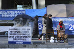 A protester sits next to a statue symbolizing a wartime sex slave to demand full compensation and an apology for wartime sex slaves near the Japanese Embassy in Seoul, South Korea, Friday, Jan. 8, 2021. A South Korean court on Friday ordered Japan to financially compensate 12 South Korean women forced to work as sex slaves for Japanese troops during World War II, the first such ruling expected to rekindle animosities between the Asian neighbors. The sign reads