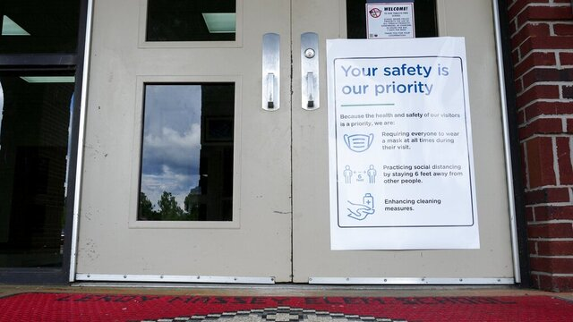 A sign outlining safety measures hangs on the door at Leroy Massey Elementary School on Tuesday, July 28, 2020, in Summerville, Ga. Thursday is the first day of school for over 2,600 students in the Chattooga County Schools system. As other districts around the state delayed their back-to-school days or moved to all-remote learning, Chattooga County school officials are going ahead with its plan to start school Thursday, one of the earliest start days in the nation. (C.B. Schmelter/Chattanooga Times Free Press via AP)