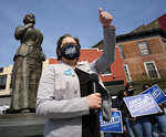 Sen. Jennifer McClellan, D-Richmond, gives a thumbs-up to a passing motorist who blew the horn as she was holding a press conference to discuss her gubernatorial campaign beneath the Maggie L. Walker statue in Richmond, Va., Thursday, April 8, 2021. (Bob Brown/Richmond Times-Dispatch via AP)