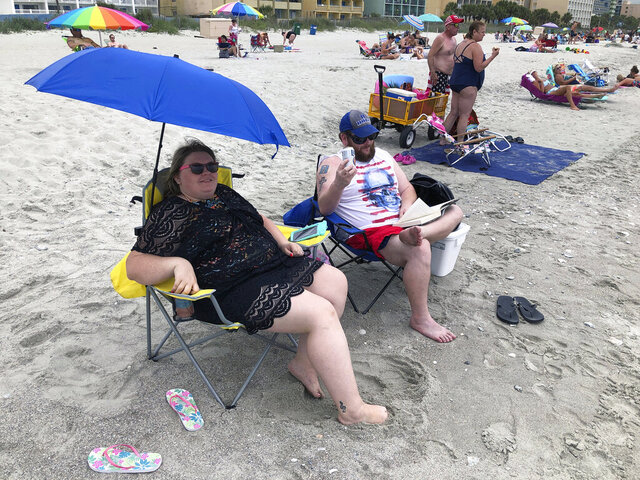 """Tabatha Johnson, left, and her husband, Mark, enjoy the first day of vacation, Thursday, June 18, 2020, in Myrtle Beach, S.C. Across America, people are leaving their cares — and sometimes their masks — at home after months of worry about the virus as Southern states like South Carolina open hotels and restaurants and like Myrtle Beach advertise """"Yes, the beach is open!"""" (AP Photo/Jeffrey Collins)"""