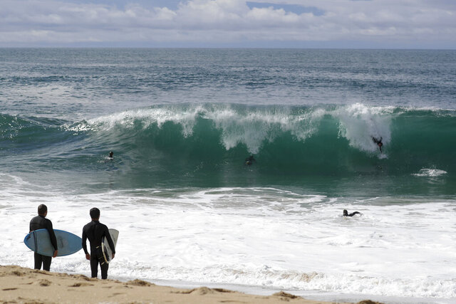 Surfers watch as body surfers ride a wave the