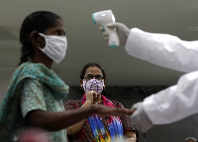 A health worker screens residents for COVID-19 symptoms in Mumbai, India, Friday, July 17, 2020. India crossed 1 million coronavirus cases on Friday, third only to the United States and Brazil, prompting concerns about its readiness to confront an inevitable surge that could overwhelm hospitals and test the country's feeble health care system. (AP Photo/Rajanish Kakade)
