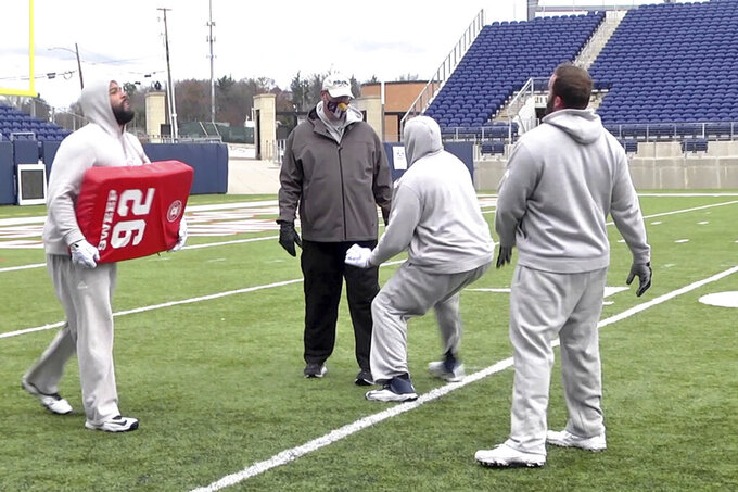 In this image provided by WaV Sports & Entertainment + The NFL Alumni Academy, Mike Tice, second from left, coaches at the NFL Alumni Academy at Tom Benson Stadium in Canton, Ohio on Nov. 4, 2020. In normal times, NFL teams sometimes must scramble to find players during the season when a wave of injuries or other issues hit. In 2020, multiply those needs exponentially because of the coronavirus pandemic. Helping out the 32 teams on a limited scale, for now, is the NFL Alumni Academy. (Devon Dalton/WaV Sports & Entertainment + The NFL Alumni Academy via AP)