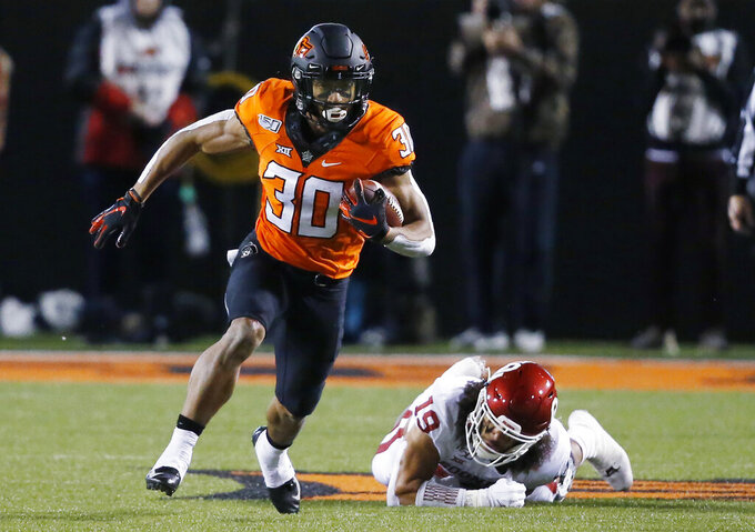 FILE - In this Nov. 30, 2019, file photo, Oklahoma State running back Chuba Hubbard (30) carries past Oklahoma linebacker Caleb Kelly during an NCAA college football game in Stillwater, Okla. Hubbard was selected to The Associated Press preseason All-America first-team, Tuesday, Aug. 25, 2020. (AP Photo/Sue Ogrocki, File)