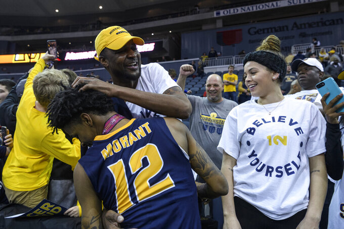 Murray State's Ja Morant (12) receives a hug from his father, Tee Morant, following the team's win in an NCAA college basketball game against Belmont for the Ohio Valley Conference men's tournament championship in Evansville, Ind., Saturday, March 9, 2019. (Sam Owens/Evansville Courier & Press via AP)